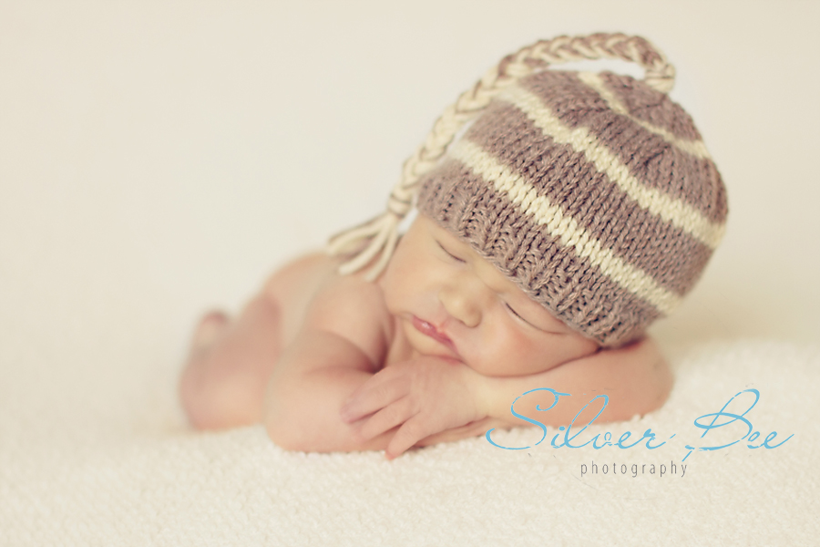 newborn boy sleeping on cream blanket with striped knitted hat