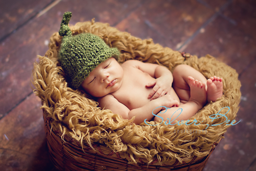 Green newborn boy hat sleeping in basket with faux fur Cedar Park Tx.