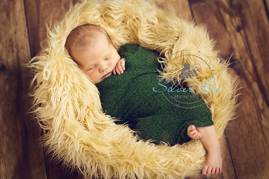 Austin-Newborn-baby-boy-sleeping-on-tan-faux-fur-in-basket-on-wood-floor
