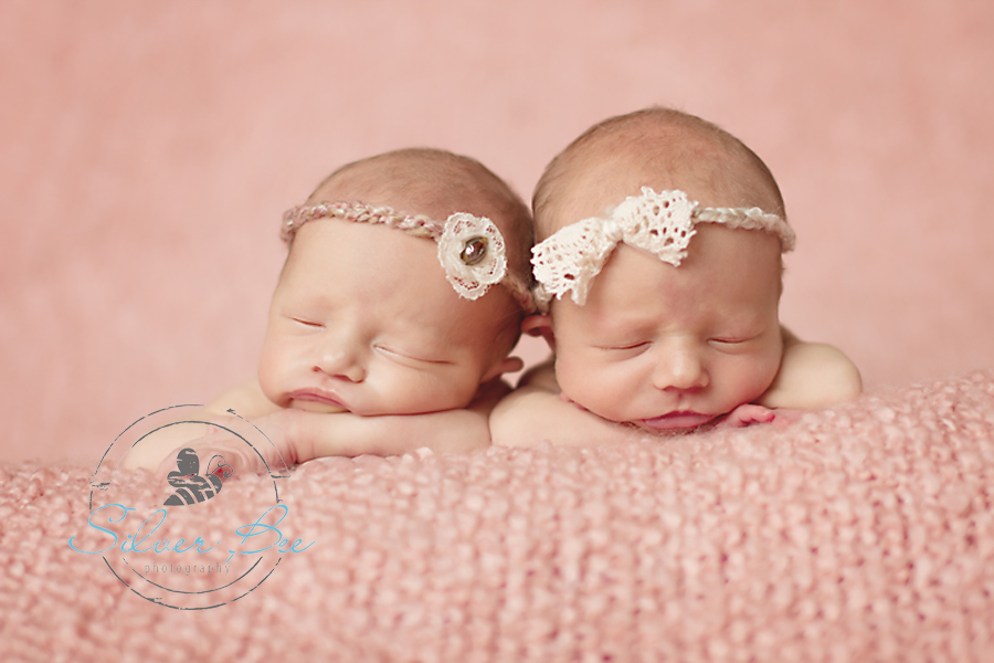 Identical twin baby girls sleeping on pink blanket with headbands by creme de la baby