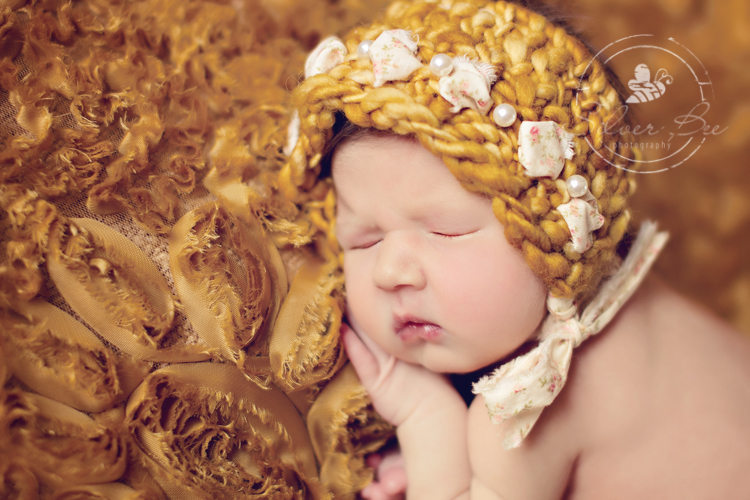 7 day old newborn girl posing on gold ruffled fabric with gold knitted and fabric bonnet, Austin Texas.