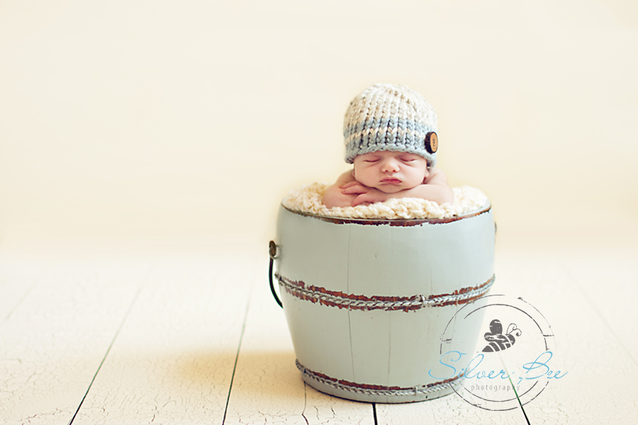 10 day old newborn boy in antique bucket with striped wool hat in Ausin Texas.
