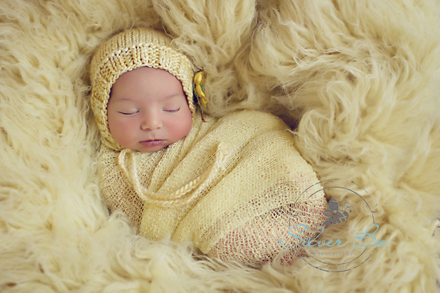 Seven day old newborn baby girl with light yellow flokati rug, yellow bonnet and yellow stretch wrap in Austin Texas.girl with light yellow flokati rug, yellow bonnet and yellow stretch wrap in Austin Texas.