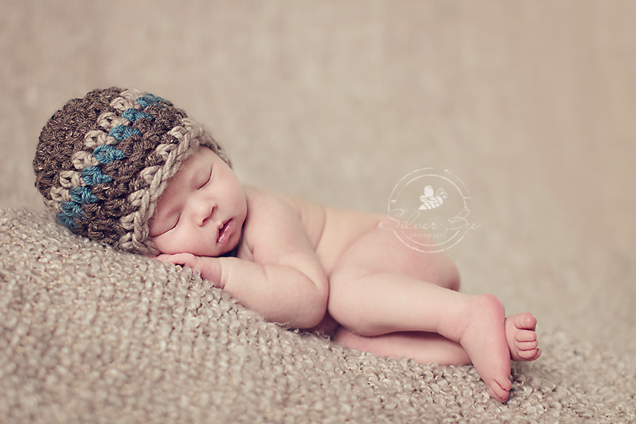 Austin newborn baby boy photo session sleeping on brown boucel blanket with striped earflap hat.