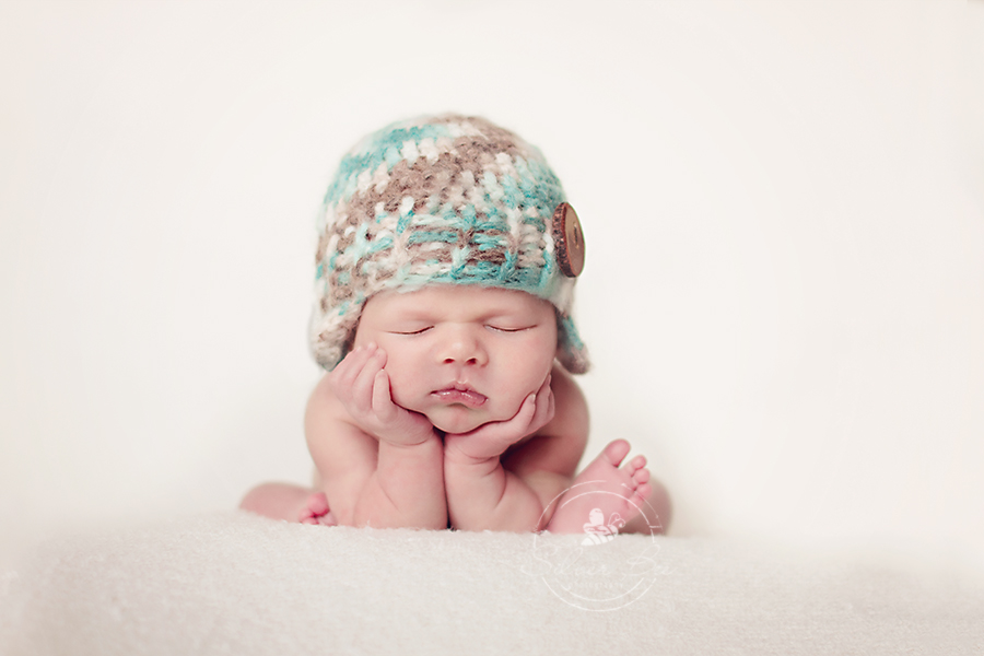 Newborn baby boy doing froggie pose with blue and brown earflap beanie hat in Austin Texas.