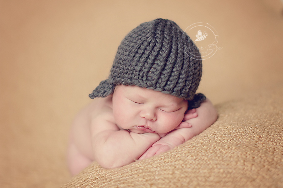 One week old newborn baby boy sleeping for newborn photo session on golden boucle blanket and dark gray aviator knitted hat in Austin Texas.