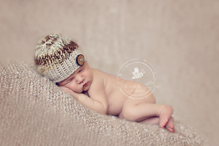 Fall colored newborn baby boy photo session with brown striped knitted hat and brown boucle blanket in Cedar Park Texas.