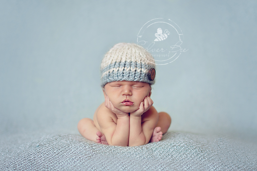 One week old baby boy in froggie pose with striped blue hat and blue texture blanket in Austin Texas newborn photography session.