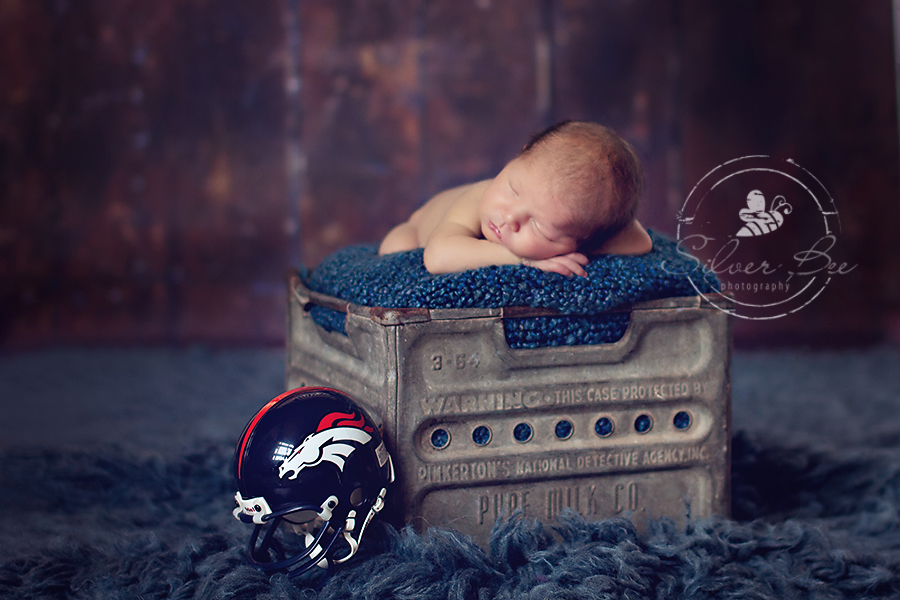 Austin TX baby boy sleeping in metal milk crate with blue boucle blanket and Denver Broncos baby helmet.