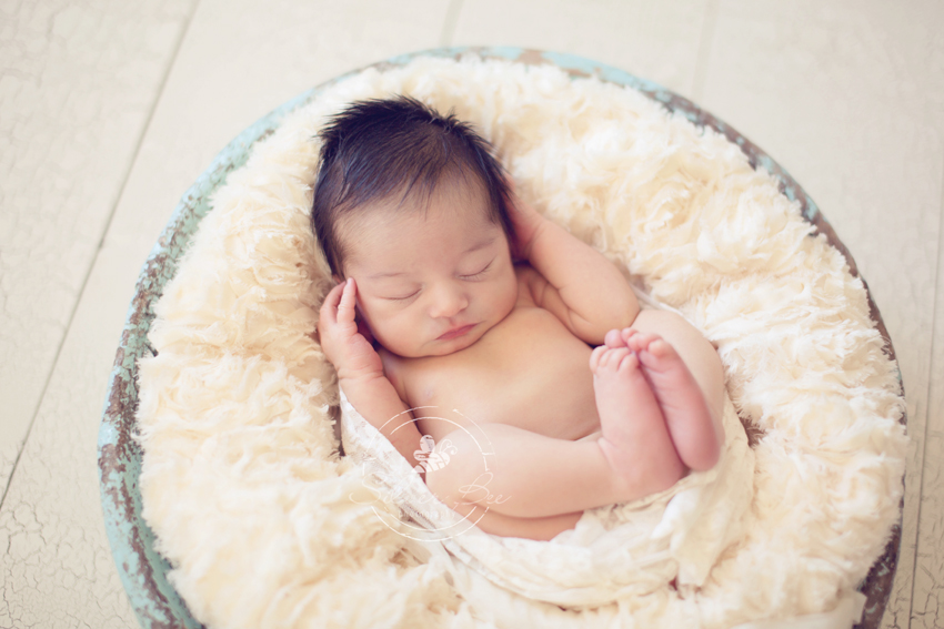 Newborn baby girl sleeping in blue bown at photo session in Austin Texas