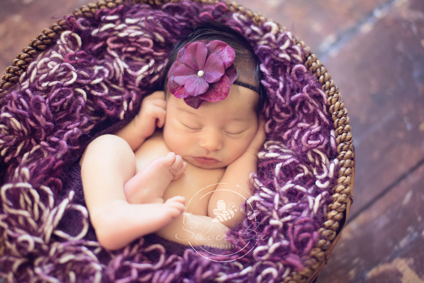 Newborn baby girl photography session with purple basket stuffer and purple bow Austin Texas.