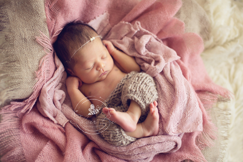 Newborn photo session in Austin Texas with pink layering set and newborn pants prop.