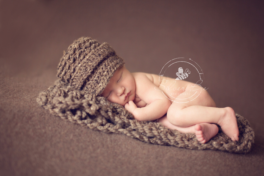 Austin Texas newborn baby is sleeping for his photography session with a brown brim hat and blanket.