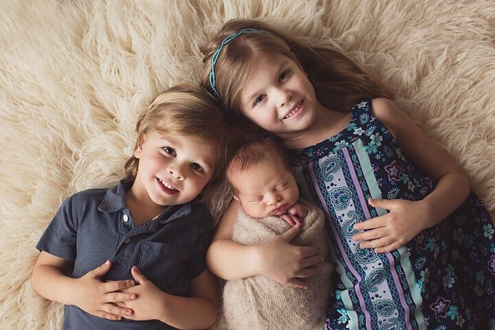 Big sister and big brother taking photo with newborn brother