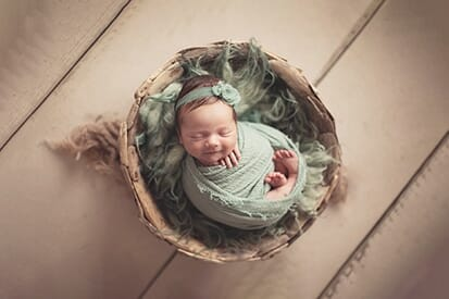 newborn wrapped in sage and posed in bowl